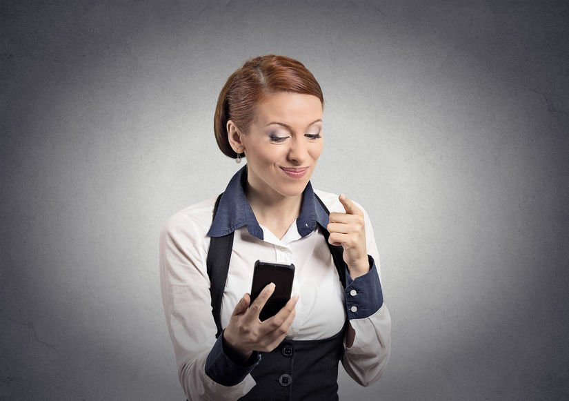 Closeup portrait angry young business woman annoyed worker pissed off employee while on mobile pointing with finger at smart phone isolated grey wall background. Negative emotion facial expression
